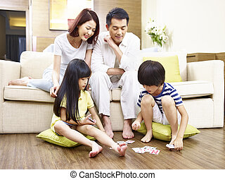 asian children playing cards while parents watching