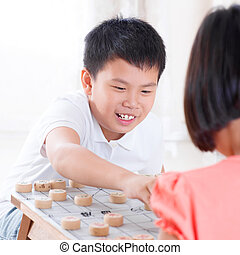 Asian children playing Chinese chess at home.