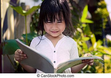 asian children reading a book in home garden