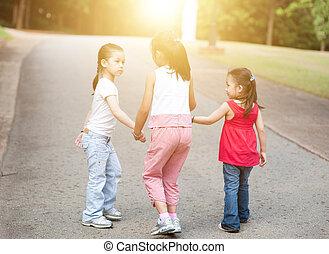 Asian children walking outdoor.
