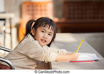 asian children with yellow pencil in hand doing school home work with happiness emotion