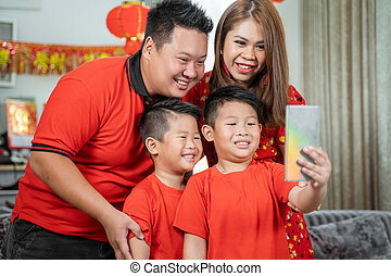 Asian chinese family with two son smiling holding cell phone to take selfie with father and mother