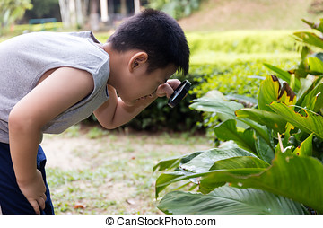 Asian Chinese little boy looking through magnifying glass