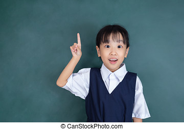 Asian chinese little girl in uniform pointing finger up