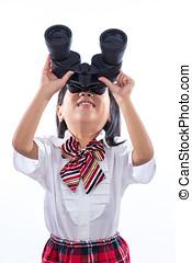 Asian Chinese little girl looking through binoculars