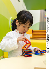 Asian Chinese little girl playing colorful magnet plastic blocks kit
