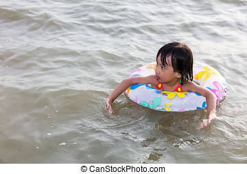 Asian Chinese little girl swimming at the seaside