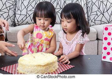 Asian Chinese little sister cutting birthday cake