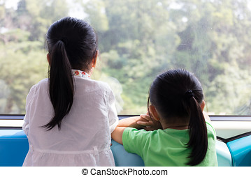 Asian Chinese little sisters inside a MRT transit looking...