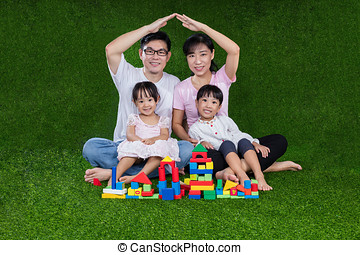 Asian Chinese parents and daughters playing blocks on the grass