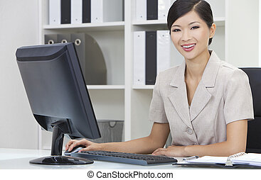 Asian Chinese Woman or Businesswoman Using Computer In Office