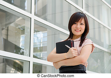 Asian college female student on campus holding a notepad