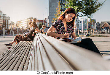 Asian college student sitting on a campus bench studying