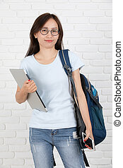 Asian College Student Smiling Holding Laptop on brick wall Background.