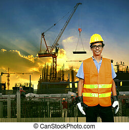 asian construction site worker smiling face and building construction site background