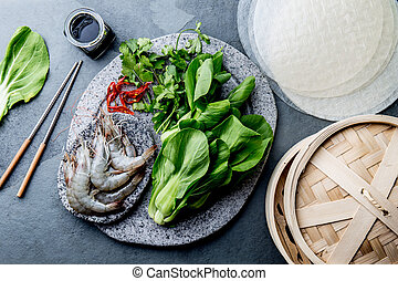 Asian cooking ingredients: rice papper, pok choy, sauces, raw shrimps. Asian food concept Chinese or Thai cuisine.