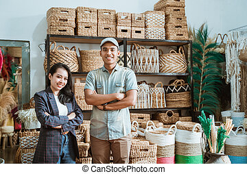 asian couple entrepreneur with crossed hands with handmade crafts on the shelf background