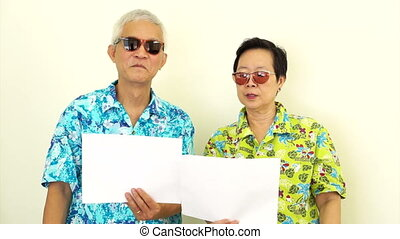 Asian couple holding white sign