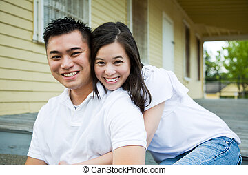 Asian couple in front of their house