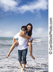 Asian Couple in love enjoy summer holiday on the beach