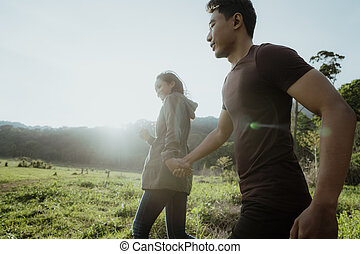 asian couple running together in nature