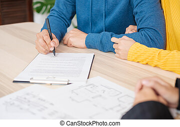 Asian couple sign home contract with realtor at home. buying new house real estate.