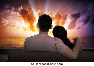 Asian couple sitting on couch watching the sunset