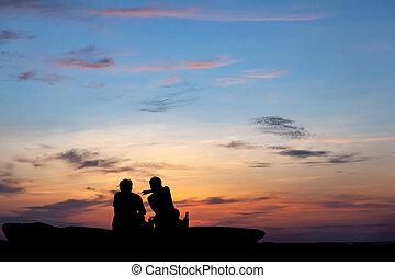 Asian couple sitting on the beach
