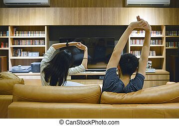 Asian couple stretching out their arms in front of TV at night