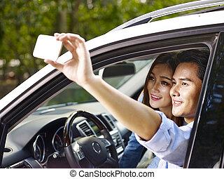 asian couple taking selfie in car