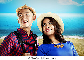 Asian couple travel along on the beach