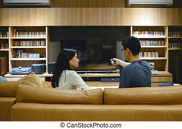 Asian couple using a remote control to turn on TV with blank screen