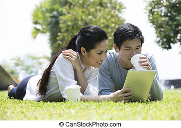 Asian couple using tablet in urban city park.