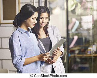 asian coworkers working together in office