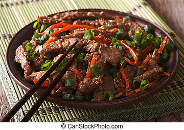 Asian cuisine: slices of beef fried with sesame and carrot ...