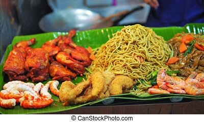 Asian cuisine, traditional dishes, street food on the night market, rice and noodles with seafood, travel and tourism
