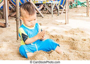 Asian cute boy playing sand on the beach