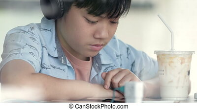 Asian cute boy using cell phone and sipping milk in the cup and smiles. Concept of: social network, message, technology.