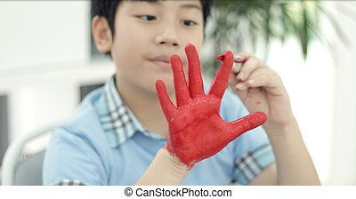 Asian cute child painting water colour on your hand .