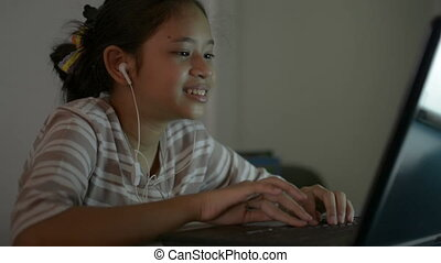 Asian cute girl student wearing earphones and talking with teacher from laptop during learning lesson online. Female teenager studying from home with video call.