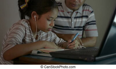 Asian cute girl wear earphones with her father using laptop for lesson online during doing homework. Father helping and teaching her daughter study from home with video call.
