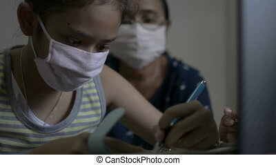 Asian cute girl with her mother wearing protective mask watching lesson online during doing homework. Mother teaching her daughter studying from home with video call.