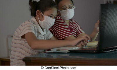 Asian cute girl with her mother wearing protective mask watching lesson online from laptop during doing homework. Mother helping and teaching her daughter study from home with video call.