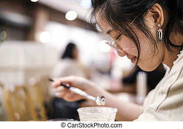Asian cute woman drinking chocolate frappe in cafe shop