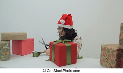 Asian cuts green ribbon to make bow for decoration box for Christmas, New Year.