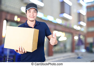 Asian Delivery man thumbs up with cardboard box on blurred background.