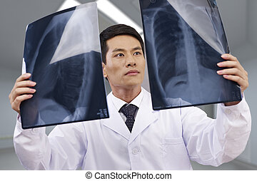 asian doctor at work - asian doctor looking at x-ray films.