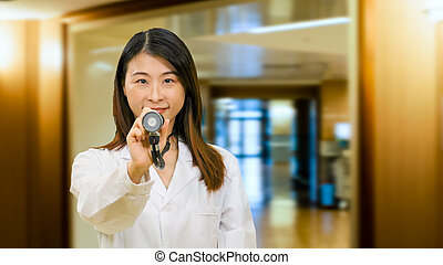 Asian doctor in hospital holding out stethoscope