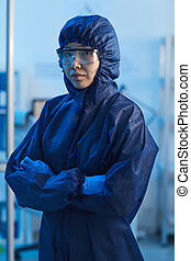 Portrait of Asian female doctor in protective workwear standing with arms crossed and looking at camera at hospital