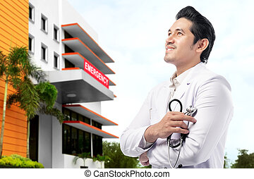 Asian doctor man with stethoscope standing in front of the emergency room